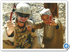 Soldier Sharing his Snack Sticks with an Afgan child